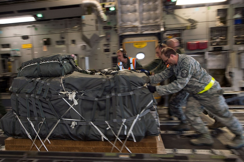 Airmen from Joint Base Elmendorf-Richardson push more than 12,000 pounds of cargo into the back of a C-17 Globemaster III at JBER, Alaska, March 2, 2016.  (U.S. Air Force photo by Staff Sgt. Sheila deVera)