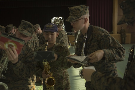 A Japan Ground Self Defense Force Western Army Band member helps Sgt. Michael A. Parker and Lance Cpl. Ivan E. Arden with queues during a rehearsal for the Western Army Band's Music Festival Mar. 3 in an auditorium on Camp Kengun. The Marines will be marching out with the Western Army in sync from separate sides of a stage and meet in a joint formation. The music festival marks the 60th anniversary of the Western Army band. (U.S. Marine Corps photo by Cpl. Tyler Ngiraswei/ Released)