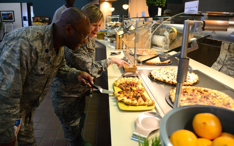 Lt. Col. Curtis Hudson, 27th Special Operations Medical Support Squadron commander, and Lt. Col. Barbara Cain, 27th Special Operations Medical Operations Squadron commander, enjoy free samplings of food during the grand opening of the Pecos Trail Dining Facility March 3, 2016, at Cannon Air Force Base, N.M. Leaders noted that they are diligently working toward creating an environment for Airmen and families to thrive, and this is simply another milestone in that journey. (U.S. Air Force photo/Staff Sgt. Alexx Pons)