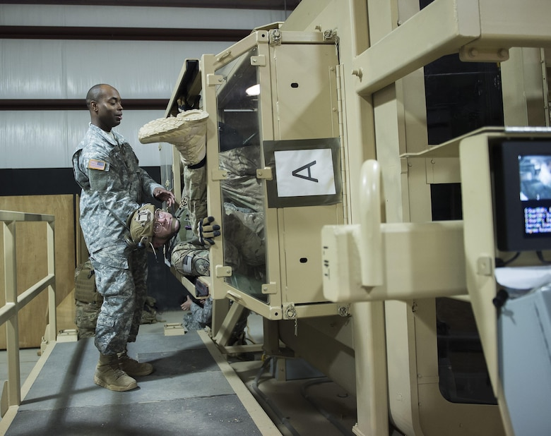 Sgt. 1st Class Ken Shirley, a Humvee egress instructor at the McCrady Battle Simulation Center, assists a combat camera Airman March 3, 2016, during exercise Scorpion Lens 2016, at McCrady Training Center on Fort Jackson, S.C. The exercise is an annual training requirement incorporating combat camera job qualification standards and advanced weapons and tactical training with Army instructors. (U.S. Air Force photo/Staff Sgt. Jared Trimarchi)