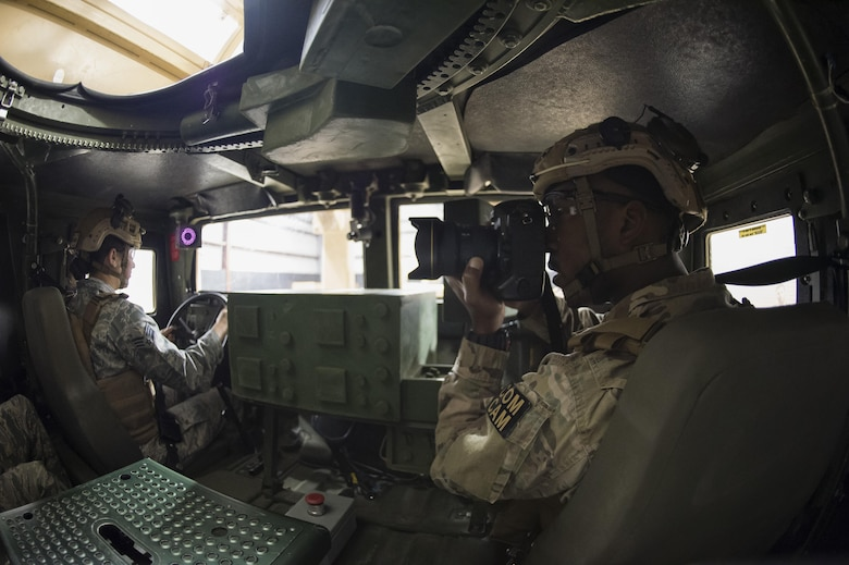 Staff Sgt. Paul Labbe, a 1st Combat Camera Squadron combat photojournalist, takes a photo inside a Humvee egress simulator March 3, 2016, during exercise Scorpion Lens 2016, at McCrady Training Center on Fort Jackson, S.C. The exercise is an annual training requirement incorporating combat camera job qualification standards and advanced weapons and tactical training with Army instructors. (U.S. Air Force photo/Staff Sgt. Jared Trimarchi)