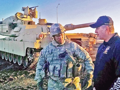 "Retired Command Sgt. Maj. George DeSario, the director of the Office of the Chief of Armor, gives advice to Sgt. 1st Class Avery Cunningham, senior enlisted leader of Company C, 3rd Battalion, 66th Armor Regiment, 1st Armored Brigade Combat Team, 1st Infantry Division, during winter gunnery Jan. 26 at Fort Riley. DeSario is an honorary command sergeant major of the ""Black Knights."""