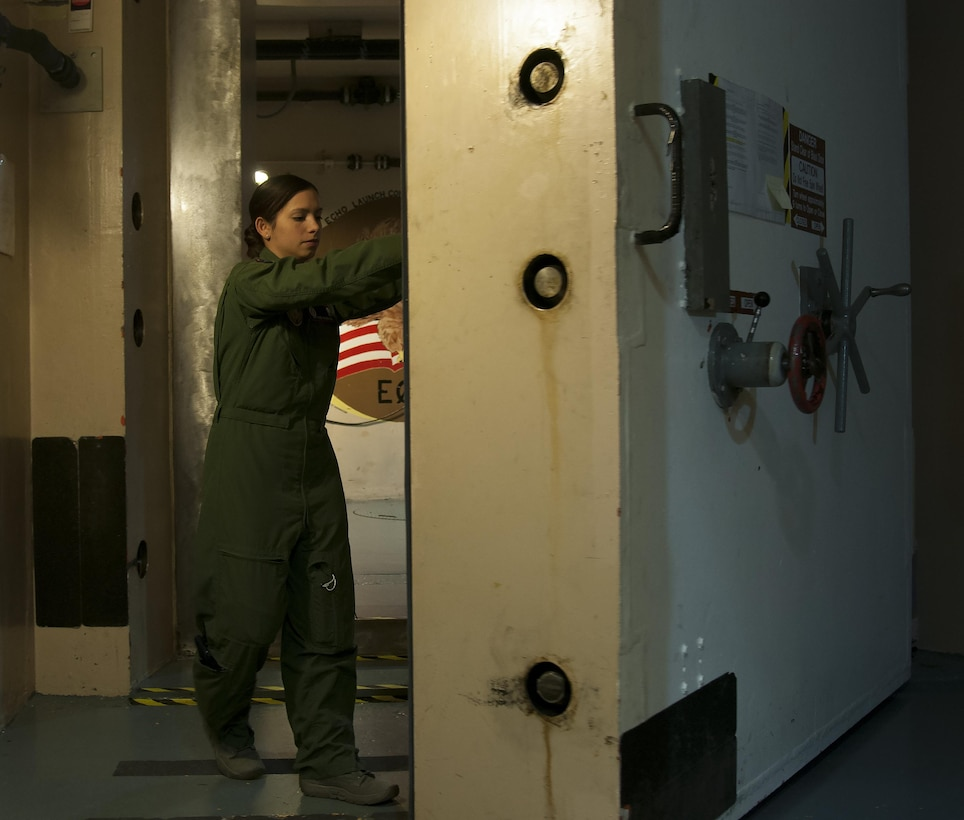 First Lt. Pamela Blanco-Coca, 319th Missile Squadron missile combat crew commander, closes the blast door underground at a Missile Alert Facility in the F.E. Warren Air Force Base, Wyo., missile complex Feb. 9, 2016. Heavy blast doors add to the survivability of the capsules and crews, in turn improving the ICBM force's deterrence capability. (U.S. Air Force photo by Senior Airman Jason Wiese)
