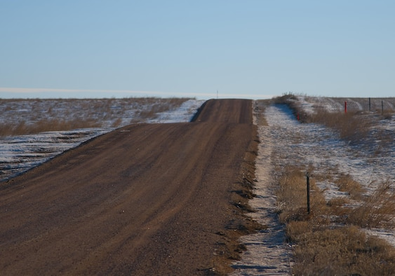 This photo depicts a hilly stretch of gravel road in the F.E. Warren Air Force Base, Wyo., missile complex. A combined total of more than 7 million miles is driven by Mighty Ninety Airmen annually. Much of the driving is done over roads like these, which can be especially hazardous in the winter, so all base personnel traveling in the missile complex receive specialized training for these conditions. (U.S. Air Force photo by Senior Airman Jason Wiese)