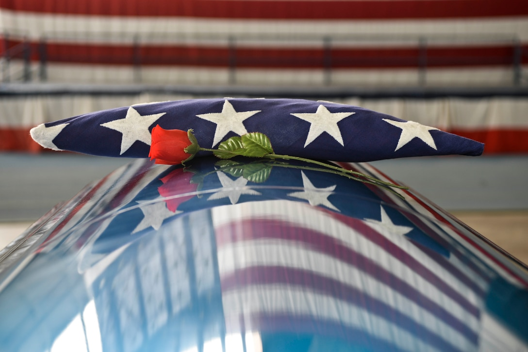 A folded flag sits on a casket during ceremonial funeral training at Ellsworth Air Force Base, S.D., Feb. 22, 2016. Search and recovery teams are in charge of finding, identifying and recovering remains of those who were lost in any incident, then bringing that individual back to their duty location where a ceremonial funeral is held. (U.S. Air Force photo by Airman Sadie Colbert/Released)