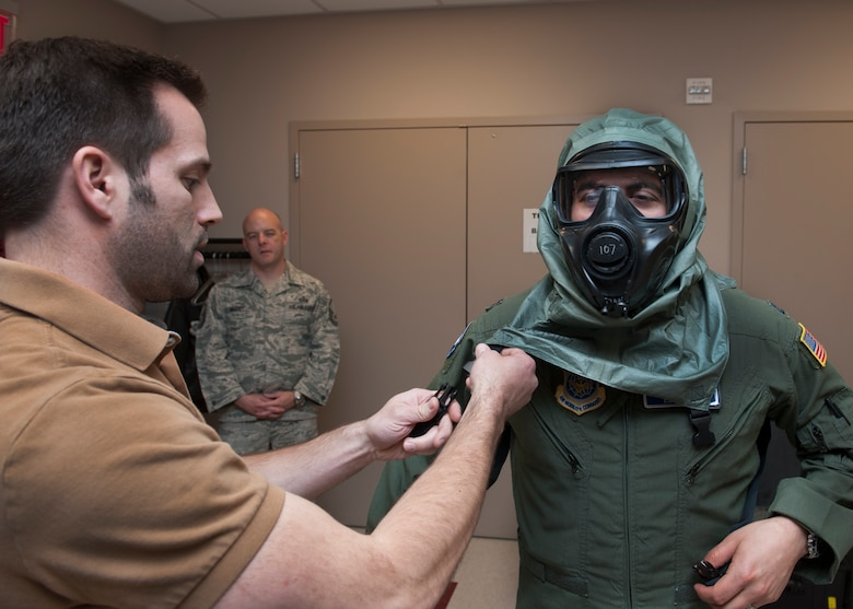 Capt. Edward Silva, 436th Operations Support Squadron Aircrew Flight Equipment commander, puts on the XM69 Aircrew Chemical, Biological, Radiological and Nuclear Defense (CBRN) system and is assisted by Steve Leadore, Joint Service Aircrew Strategic Program team test analyst, March 2, 2016, inside the Aircrew Flight Equipment facility on Dover Air Force Base, Del. The Air Force, Army, Navy and Marine Corps all utilize their own unique aircrew CBRN system. The XM69 is being developed as a single system that will be utilized by all four branches. (U.S. Air Force photo/Senior Airman Zachary Cacicia)