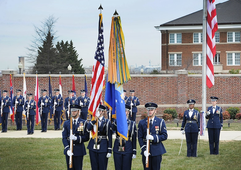 Members of the United States Air Force Honor Guard present the nation's colors during a ceremony to recognize four of the first five female enlisted ceremonial guardsmen at Joint Base Anacostia-Bolling, Mar. 8. The event included a formal lawn ceremony, a ribbon-cutting to christen a display case honoring the first women to join the Air Force Honor Guard, and a panel discussion. (U.S. Air Force photo/Jim Lotz)