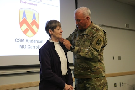 """Maj. Gen. Leslie Carroll (right), the commanding general for the 377th Theater Sustainment Command presents a length of service certificate and emblem to Margaret """"Peggy"""" Ranschaert in honor of her 45-year career of service as an Army civilian employee  during a length of service ceremony held March 4 at the Spc. Luke P. Frist Army Reserve Center at Fort Benjamin Harrison, Ind."""