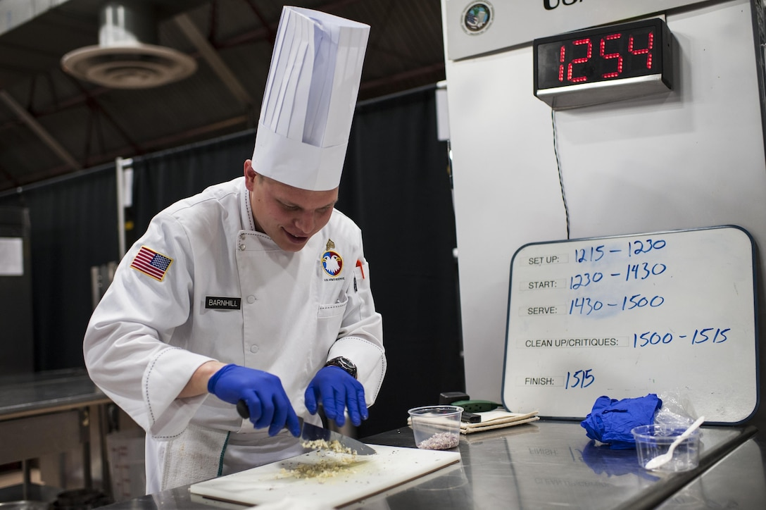 U.S. Army Reserve Culinary Arts Team member Sgt. Joshua Barnhill, with the 377th Theater Sustainment Command, chops ingredients during the Nutritional Hot Food Challenge category at the 41st Annual Military Culinary Arts Competitive Training Event, March 8, 2016, at Fort Lee, Va. Parker and Barnhill earned a silver in the category with their roasted beet salad, pan-seared trout, and eggless, milkless spice cake, all coming in at under 850 calories. (U.S. Army photo by Timothy L. Hale) (Released)