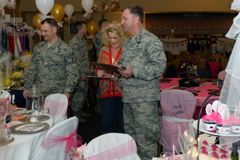Chief MSgt. Shane Wagner (left), 4th Fighter Wing command chief, Sarah Merritt (center), the Arts Council of Wayne County executive director, and Col. Mark Slocum (right), 4th Fighter Wing commander, judge tables for the inaugural Spouses Dining-in, March 5, 2016, at Seymour Johnson Air Force Base, North Carolina. The tables were judged on elements such as creativity, hand-made items and originality. (U.S. photo/Airman 1st Class Ashley Williamson)