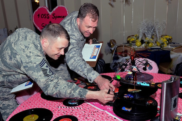 Chief MSgt. Shane Wagner (left), 4th Fighter Wing command chief, and Col. Mark Slocum (right), 4th Fighter Wing commander, inspect a table for the first-ever Spouses Dining-in, March 5, 2016, at Seymour Johnson Air Force Base, North Carolina. Approximately 100 people attended the dining-in dressed as characters from the movie theme of their squadron's table. (U.S. photo/Airman 1st Class Ashley Williamson)