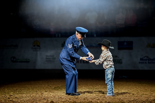 U.S. Army and Air Force veteran Master Sgt. Tom Davis receives a folded American flag from a young local resident during the opening ceremony for Military Appreciation Night as part of the 84th annual San Angelo Stock Show and Rodeo at Foster Communications Coliseum in San Angelo, Texas, Feb. 17, 2016. The rodeo honored military members from all generations. (U.S. Air Force photo by Senior Airman Devin Boyer/Released)