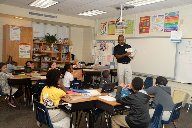 Lt. Col. Nathaniel Robinson, executive officer, Marine Corps Logistics Base Albany, reads to attentive 3rd graders at Radium Springs Elementary School, Albany, Ga., during the Read Across America initiative, recently. The annual event is held to celebrate the birthday of author/cartoonist, Dr. Seuss.