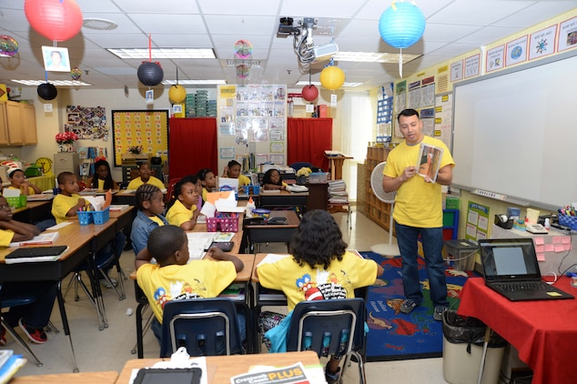 Capt. Jose Castillo, inspector-instructor, Detachment 2, Supply Company, Combat Logistics Battalion 453, 4th Marine Logistics Group, Marine Corps Logistics Base Albany, reads to 4th-grade students at International Studies Charter School, Albany, Ga., recently. The event was a part of the annual Read Across America activities, which celebrate the birthday of author, illustrator Theodor Seuss Geisel, better known as Dr. Seuss.