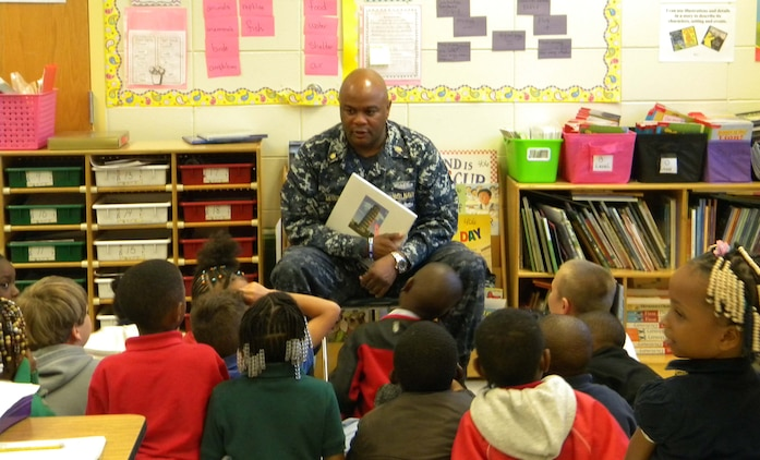 Lt. Cmdr. Donald Mitchell, senior nurse executive, Naval Branch Health Clinic-Albany, located at Marine Corps Logistics Base Albany, reads to a group of students at Alice Coachman Elementary School, Albany, Ga., during the Read Across America activities. The recent event is held nationally to commemorate the birthday of author/illustrator, Theodor Seuss Geisel, better known as Dr. Seuss.