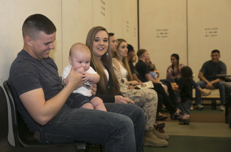 Pfc. Braxton Peirce, radio operator, 2nd Battalion, 7th Marine Regiment, plays with his son Reminton, 6 months, before the units' pre-deployment brief at building 1707 aboard the Combat Center, March 2, 2016. (Official Marine Corps photo by Cpl. Thomas Mudd/Released)
