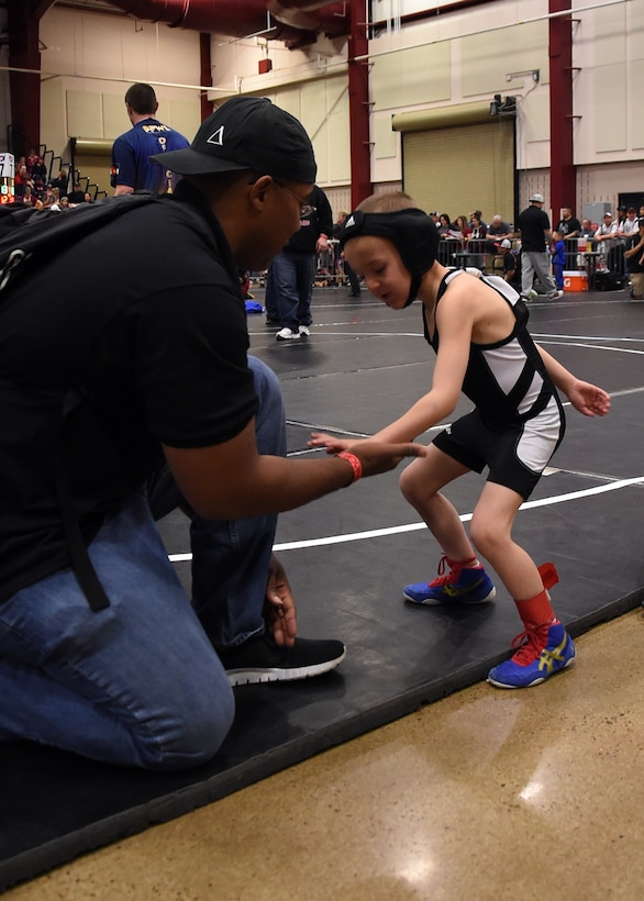 Morris Thomas, Children of Valor wrestling team coach, gives Ian Greer a low-five before his first match at the state wrestling competition in Castle Rock, Colorado, Feb. 28, 2016. Children of Valor has only been a team for 11 months, but placed fifth out of 191 teams during the tournament. (U.S. Air Force photo/Staff Sgt. Debbie Lockhart)