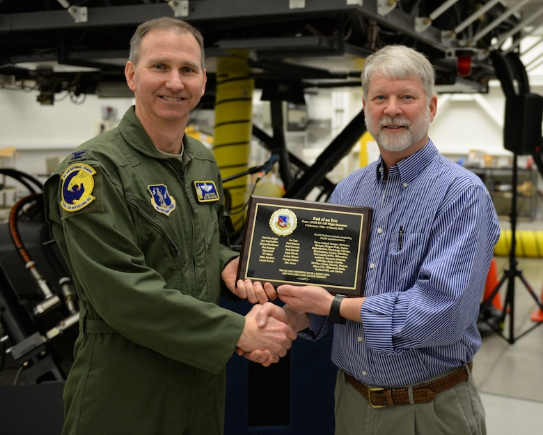U.S. Air Force Colonel James Ryan, 157th Air Refueling Wing commander, New Hampshire Air National Guard, presents a plaque to Mr. Jon VanGuilder, regional site manager for Delaware Resource Group, during the retirement of the KC-135 flight simulator, Pease Air National Guard Base, New Hampshire, March, 9, 2016. DRG supports the daily operation of the simulator.  The simulator is being retired to make way for a new KC-46 weapons trainer slated to arrive in the spring of 2017. (U.S. Air National Guard photo by Staff Sgt. Curtis J. Lenz)