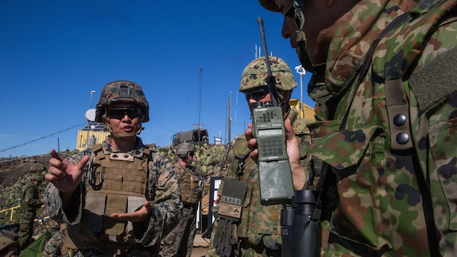 A U.S. Marine Corps interpreter attached to 1st Air Naval Gunfire Liaison Company translates radio messages for a soldier with Western Army Infantry Regiment, Japan Ground Self-Defense Force, during a supporting arms coordination center exercise on San Clemente Island, California, Feb. 22, 2016, as part of Exercise Iron Fist 2016. SACCEX  serves as a cooperative learning tool for the US-Japan partnership through the operation of a SACC, which has developed the USMC and JGSDF's ability to integrate naval gunfire, mortars and close-air support  as a combined force.