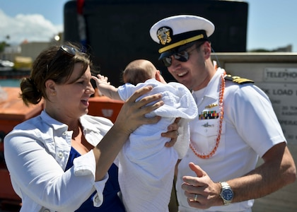 PEARL HARBOR (March 9, 2016) Lieutenant Commander Sean Gray of Nampa, Idaho, the executive officer of the Virginia-Class fast-attack submarine USS Texas (SSN 775), meets for the first time, his 7-week-old daughter, Vivian, presented to him by his wife, Jennifer, following the return of the submarine to Pearl Harbor, after completing a scheduled Western Pacific deployment. (U.S. Navy photo by Mass Communication Specialist 2nd Class Michael H. Lee/Released)
