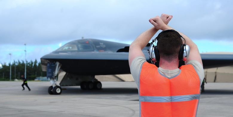 U.S. Air Force Senior Airman Adam Sweet, a crew chief from the 393rd Aircraft Maintenance Unit, prepares to marshal a B-2 Spirit while deployed at an undisclosed location in the U.S. Pacific Command area of operations March 10, 2016. Bomber crews routinely deploy to maintain a high state of readiness and crew proficiency while integrating capabilities with key regional partners. (U.S. Air Force photo by Senior Airman Joel Pfiester/Released)