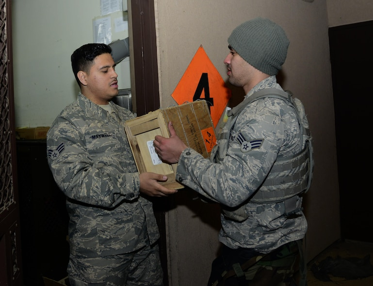 Senior Airman Sidney Maxwell, 51st Security Forces Squadron armorer, receives 50-caliber rounds from Senior Airman GianFranco Pagan Marquez, 51st SFS defender on Osan Air Base, Republic of Korea, March 10, 2016. Members working in the armory are accountable for every weapon and piece of ammunition issued to security forces Airmen. (U.S. Air Force photo by Senior Airman Kristin High/Released)