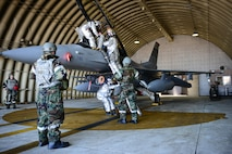 Firefighters from 51st Civil Engineer Squadron pull a mock unconscious pilot from the F-16 Fighting Falcon during readiness exercise Beverly Midnight 16-01, March 9, 2016, at Osan Air Base, Republic of Korea. First responders worked together to pull the mock pilot from F-16 to test their tactics and techniques during this exercise. Beverly Midnight 16-01 is an exercise to assess Team Osan's capabilities to defend, sustain and execute combat operations in a chemical environment. (U.S. Air Force photo by Staff. Sgt. Jonathan Steffen/Released)