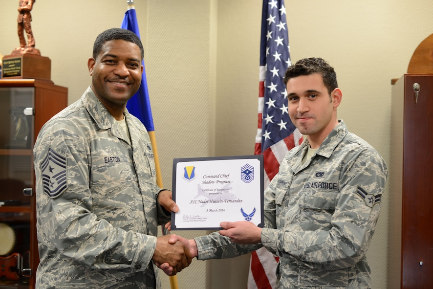 Airman First Class Nader Hussein-Fernandez, an aerospace ground equipment technician with the 86th Maintenance Squadron, receives a certificate of recognition from 86th Airlift Wing Command Chief Philip L. Easton, March 3, at Ramstein Air Base, Germany. Hussein-Fernandez was the first to participate in Easton's shadow program at Ramstein, allowing him the opportunity to witness life as a wing command chief for a duty day. (U.S. Air Force photo/Tech. Sgt. Micky M. Pena)