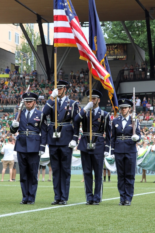 Members of the Portland Air National Guard Base Honor Guard team, from left to right, Staff Sgt. Joseph Regas, Staff Sgt. Bret Workman, Tech. Sgt. John Hughel, and Staff Sgt. Kalene Kaplan Present the Colors at the Portland Timbers soccer match against the Seattle Sounders held at Providence Park, Portland, Ore., June 28, 2015. (U.S. Air National Guard photo by Master Sgt. Shelly Davison, 142nd Fighter Wing Public Affairs/Released)