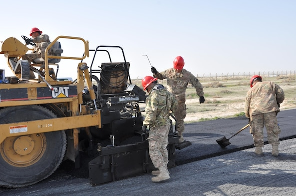Members of the 557th Expeditionary Civil Engineers Group, Red Horse, construct a 2 mile long access road at an undisclosed location in Southwest Asia, January 20, 2016.  Red Horse personnel working this paving project are deployed from the 254th in Guam, Montana's 219th, and the 210th out of New Mexico.  (U.S. Air Force photo by Master Sgt. Kevin Nichols)