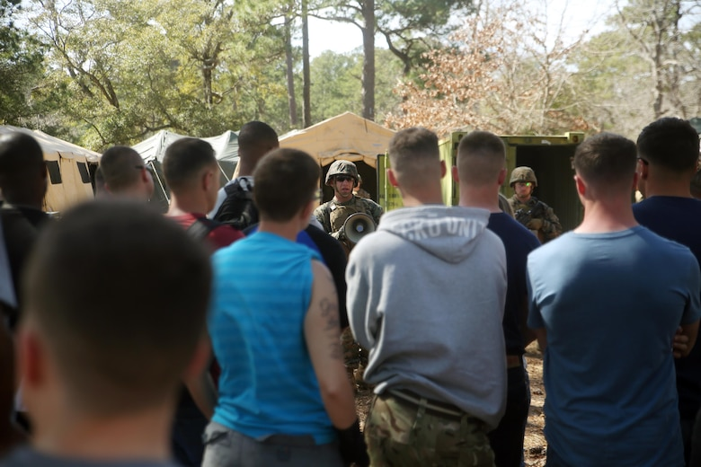 Sgt. Brandyn Knight, the Evacuation Control Center entry point noncommissioned officer in charge with Combat Logistics Battalion 2, briefs notionally displaced American citizens as they prepare to enter the ECC to be evacuated during the battalion's certification exercise, at Marine Corps Auxiliary Landing Field Bogue, N.C., March 10, 2016. The battalion is slated to deploy on Special Purpose Marine Air-Ground Task Force-Crisis Response-Africa later this year. (U.S. Marine Corps photo by Cpl. Joey Mendez)