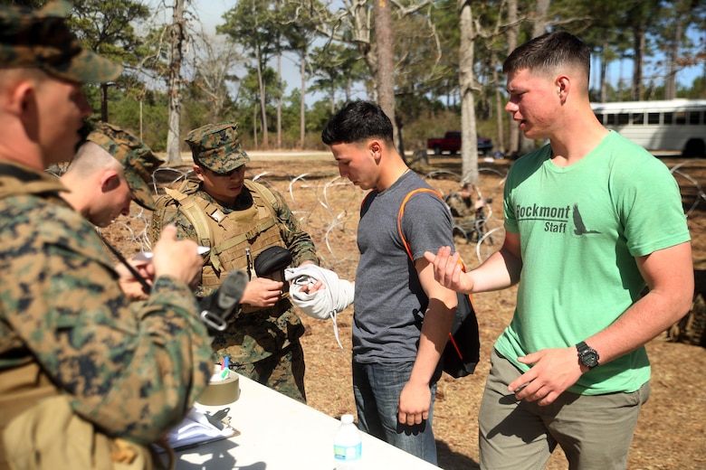 U.S. Navy Petty Officer 2nd Class James Aliviado, a hospital corpsman with Combat Logistics Battalion 2, evaluates an injury of a notionally displaced American citizen as he enters the Evacuation Control Center during the battalion's certification exercise, at Marine Corps Auxiliary Landing Field Bogue, N.C., March 10, 2016. The battalion is slated to deploy on Special Purpose Marine Air-Ground Task Force-Crisis Response-Africa later this year. (U.S. Marine Corps photo by Cpl. Joey Mendez)