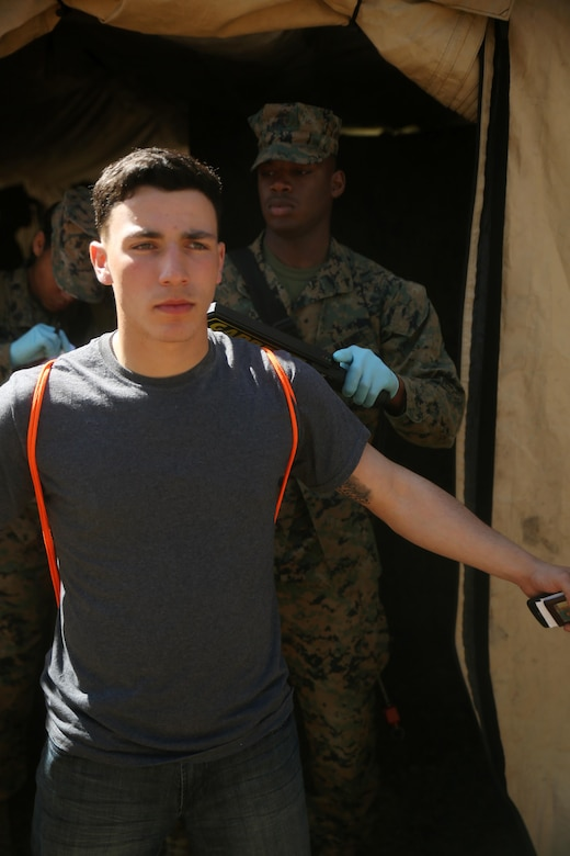 Lance Cpl. Dean Rosas, a motor vehicle operator with Combat Logistics Battalion 2, gets scanned while playing the role of a notionally-displaced citizen in need of evacuation from a foreign country in the Evacuation Control Center during the battalion's certification exercise, at Marine Corps Auxiliary Landing Field Bogue, N.C., March 10, 2016. The battalion is slated to deploy on Special Purpose Marine Air-Ground Task Force-Crisis Response-Africa later this year. (U.S. Marine Corps photo by Cpl. Joey Mendez)