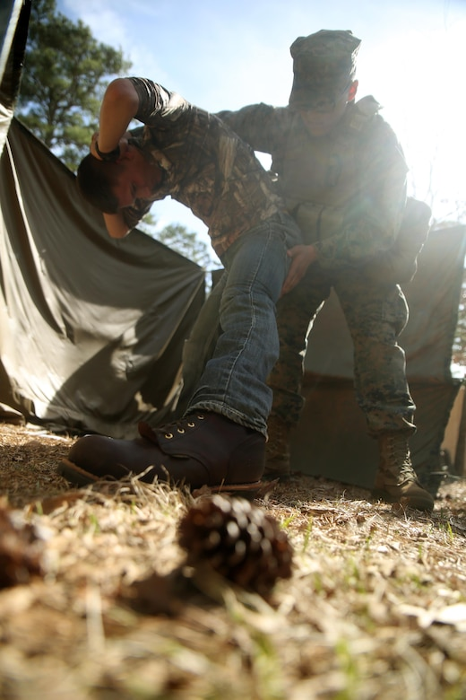 Cpl. Alex Valdez, an electro-optical ordnance repairman and the Evacuation Control Center holding noncommissioned officer in charge, searches a detainee during the battalion's certification exercise, at Marine Corps Auxiliary Landing Field Bogue, N.C., March 10, 2016. The battalion is slated to deploy on Special Purpose Marine Air-Ground Task Force-Crisis Response-Africa later this year. (U.S. Marine Corps photo by Cpl. Joey Mendez)