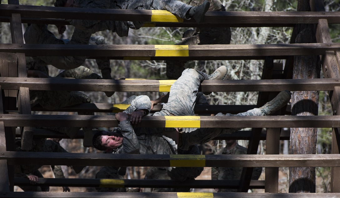 Combat camera Airmen and Soldiers weave through an obstacle on the confidence course during exercise Scorpion Lens March 6, 2016, at Fort Jackson, S.C. The purpose of the training is to provide refresher training to combat camera personnel of all ranks and skill levels in basic tactics, techniques, and procedures inherent to combat camera mission tasking. (U.S. Air Force photo/Staff Sgt. Perry Aston)