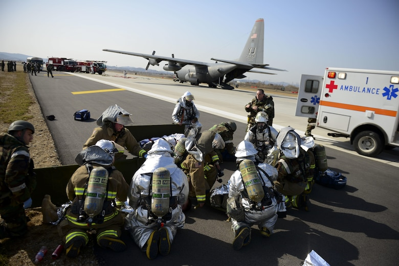 First responders from the 51st Fighter Wing provide assistance to mock wounded personnel during exercise Beverly Midnight 16-01 March 9, 2016, at Osan Air Base, South Korea. This particular exercise scenario involved a C-130H Hercules assigned to the 374th Airlift Wing from Yokota AB, Japan, which took simulated small-arms fire from opposing forces upon landing. (U.S. Air Force photo/Staff Sgt. Jonathan Steffen)