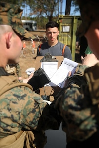 Marines with Combat Logistics Battalion 2, verify the identity of a notionally-displaced citizen at the first station of the Evacuation Control Center during the battalion's certification exercise, at Marine Corps Auxiliary Landing Field Bogue, N.C., March 10, 2016. The battalion is slated to deploy on Special Purpose Marine Air-Ground Task Force-Crisis Response-Africa later this year. (U.S. Marine Corps photo by Cpl. Joey Mendez)