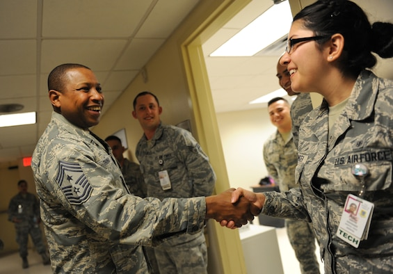 Chief Master Sgt. Farrell Thomas, 2nd Air Force command chief, recognizes Airman 1st Class Yvette Redinger, 81st Dental Squadron dental technician, by giving her a coin during an immersion tour at the Keesler Medical Center Mar.8, 2016, Keesler Air Force Base, Miss. Thomas visited the 81st Medical Group to become oriented with group missions, operations and personnel. (U.S. Air Force photo by Kemberly Groue)