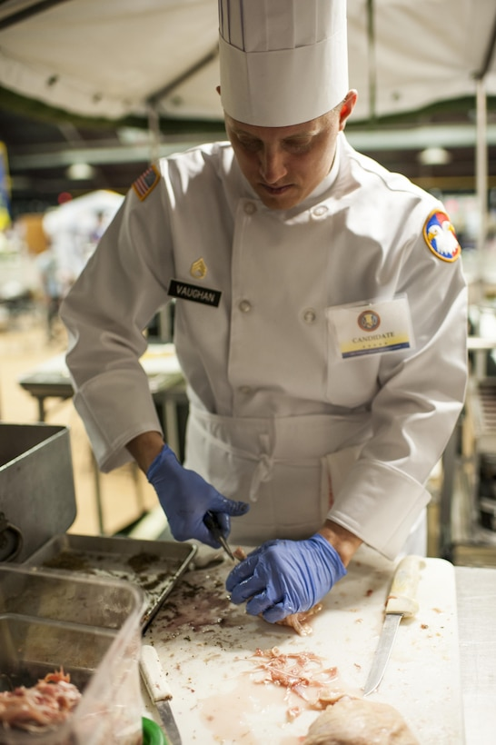 U.S. Army Reserve Culinary Arts Team member, Staff Sgt. Jeffery Vaughn, prepares chicken during the Military Hot Food Kitchen category at the 41st Annual Military Culinary Arts Competitive Training Event, March 10, 2016, at Fort Lee, Va. The team prepared Roasted Golden and Burgundy Beet Salad, Coq au Vin Nuevo (Chicken braised in red wine), and Molten Lava Cake working on a Mobile Kitchen Trailer for 45 dining guests. (U.S. Army photo by Timothy L. Hale/Released)