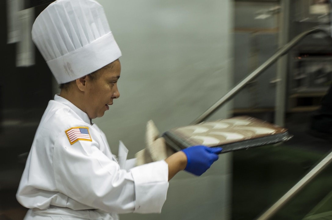 U.S. Army Reserve Culinary Arts Team member Staff Aqueelah James, moves part of her dessert to the oven during the Military Hot Food Kitchen category at the 41st Annual Military Culinary Arts Competitive Training Event, March 10, 2016, at Fort Lee, Va. The team prepared Roasted Golden and Burgundy Beet Salad, Coq au Vin Nuevo (Chicken braised in red wine), and Molten Lava Cake working on a Mobile Kitchen Trailer for 45 dining guests. (U.S. Army photo by Timothy L. Hale/Released)