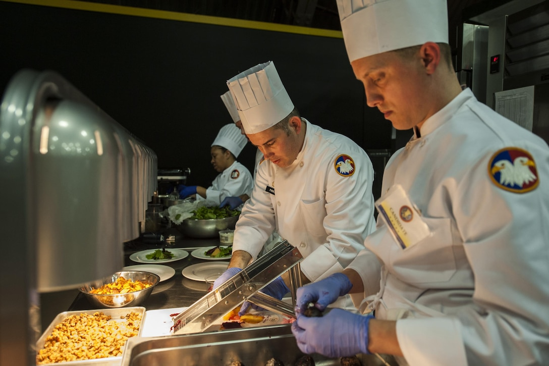 U.S. Army Reserve Culinary Arts Team members Staff Joseph Parker, center, and Staff Sgt. Jeffery Vaughn, plate the first course during the Military Hot Food Kitchen category at the 41st Annual Military Culinary Arts Competitive Training Event, March 10, 2016, at Fort Lee, Va.. The team prepared Roasted Golden and Burgundy Beet Salad, Coq au Vin Nuevo (Chicken braised in red wine), and Molten Lava Cake working on a Mobile Kitchen Trailer for 45 dining guests. (U.S. Army photo by Timothy L. Hale) (Released)