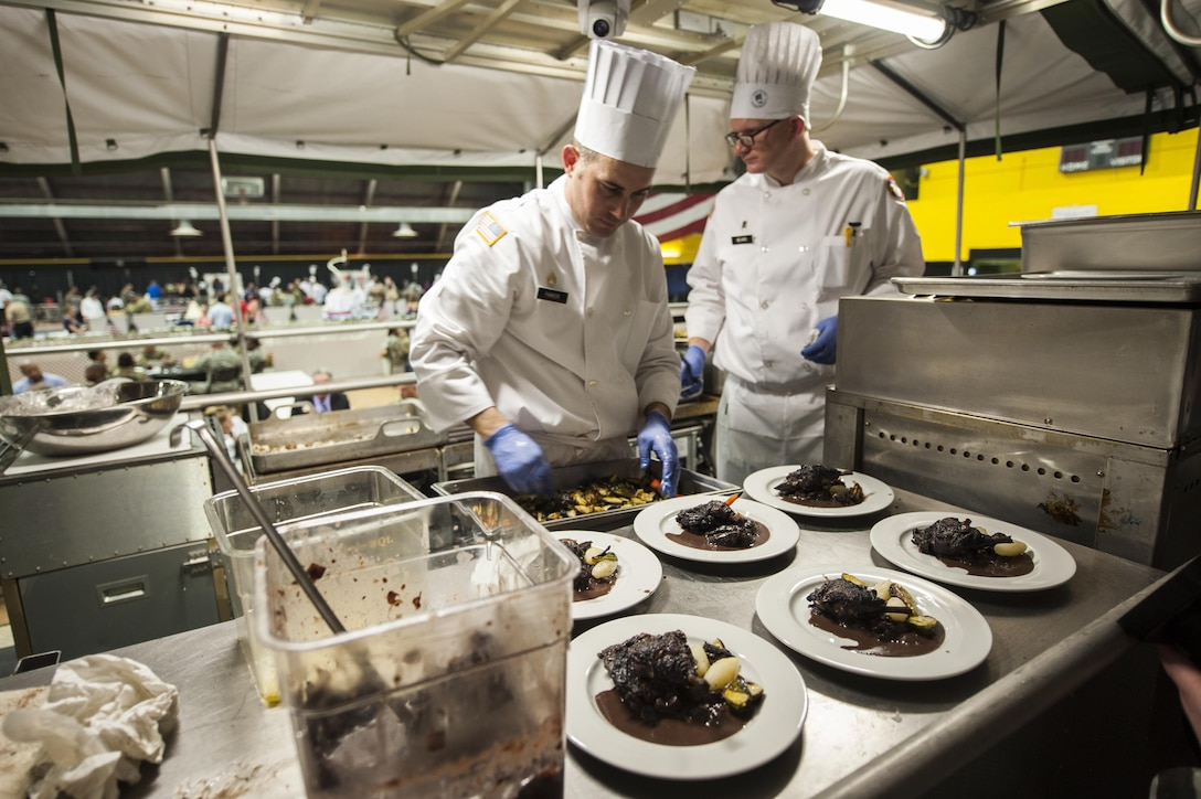 U.S. Army Reserve Culinary Arts Team captain, Staff Joseph Parker, left, and team manager, Chief Warrant Officer 2 Colby Beard, plate the main course during the Military Hot Food Kitchen category at the 41st Annual Military Culinary Arts Competitive Training Event, March 10, 2016, at Fort Lee, Va.. The team prepared Roasted Golden and Burgundy Beet Salad, Coq au Vin Nuevo (Chicken braised in red wine), and Molten Lava Cake working on a Mobile Kitchen Trailer for 45 dining guests. (U.S. Army photo by Timothy L. Hale) (Released)