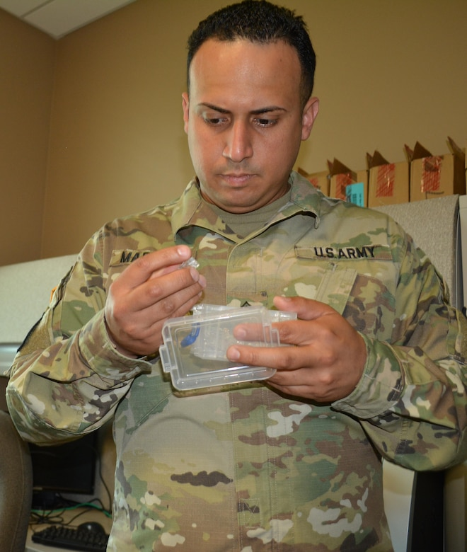 Staff Sgt. Hector Marrero, an Information Technology Specialist assigned to the 80th Training Command, searches for a wire connector at The Army School System Training Center Grand Prairie, Texas, March 7, 2016.