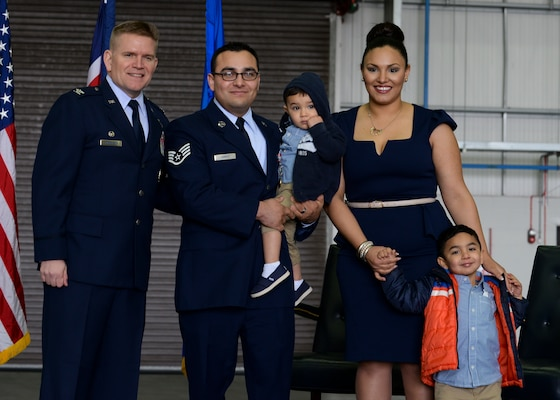 U.S. Air Force Col. Thomas D. Torkelson, 100th Air Refueling Wing commander, left, Staff Sgt. Vicente Gomez, 100th Aircraft Maintenance Squadron crew chief, and his wife and children pose for a photo during a ceremony March 11, 2016, on RAF Mildenhall, England. Gomez was presented with the Airman's Medal for risking his life to save two others near RAF Mildenhall on May 12, 2014. (U.S. Air Force photo by Senior Airman Victoria H. Taylor/Released)
