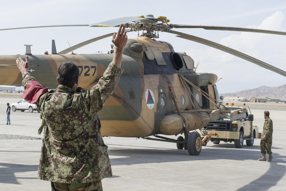 An Afghan Air Force member guides an Mi-17 helicopter, owned and operated by the Kandahar Air Wing, to a hangar to receive maintenance at Kandahar Airfield, March 2, 2016. Members of the AAF work closely with Train Advise Assist Command - Air, a U.S. run functional command, that supports NATO's Resolute Support mission assists our Afghan partners to develop a professional, capable and sustainable force. (U.S. Air Force photo/Tech. Sgt. Robert Cloys)