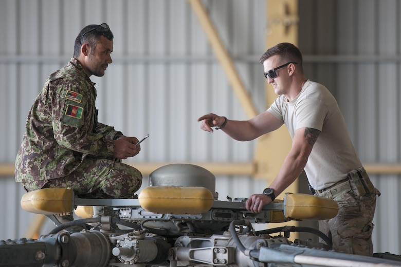 Tech. Sgt. Richard Embrey, Train Advise Assist Command - Air Mi-17 Intermediate Maintenance Squadron advisor, advises an Afghan Air Force member during a 100-hour inspection on an Mi-17 at Kandahar Airfield, March 2, 2016. As a functional command, TAAC-Air assists our Afghan partners to develop a professional, capable and sustainable force. (U.S. Air Force photo/Tech. Sgt. Robert Cloys)