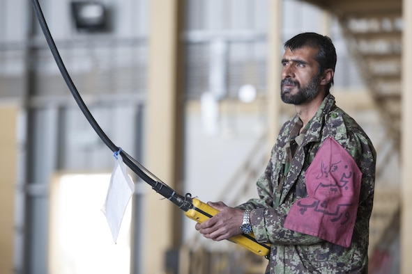 An Afghan Air Force member operates a crane to remove the blades of an Mi-17 helicopter during a 100-hour inspection at Kandahar Airfield, Afghanistan, March 2, 2016. Members of the AAF work closely with Train Advise Assist Command - Air, a U.S. run functional command, that assists our Afghan partners to develop a professional, capable and sustainable force. (U.S. Air Force photo/Tech. Sgt. Robert Cloys)