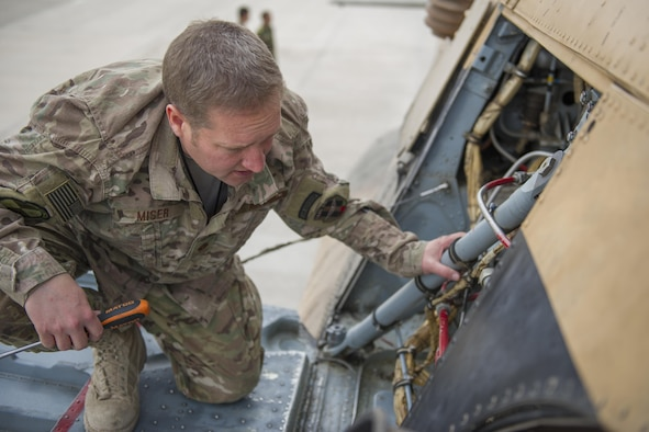 Maj. Jeffrey Miser, 441st Air Expeditionary Advisory Squadron commander, performs pre-flight checks on an Mi-17 helicopter owned by the Afghan Air Force prior to a training sortie at Kandahar Air Field, Afghanistan, March 3, 2016. TAAC-Air assists our Afghan partners to develop a professional, capable and sustainable force. (U.S. Air Force photo/Tech. Sgt. Robert Cloys)