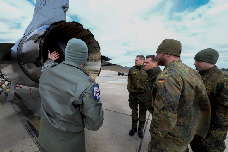 U.S. Air Force Maj. Benjamin Robbins, left, fighter pilot with the New Jersey Air National Guard's 177th Fighter Wing, explains F-16C Fighting Falcon propulsion characteristics to German armed forces Joint Terminal Attack Controllers (JTACs) participating in a five day combined training exercise with the 227th Air Support Operations Squadron (ASOS) at the Atlantic City Air National Guard Base, N.J., on Feb. 26, 2016. The German JTACs, from the 5th unit of the 131st Artillery Battalion in Weiden and the 26th Airborne Regiment in Zweibrücken, Germany, trained with JTACs from the 227th ASOS in close air support at Warren Grove Bombing Range in Ocean County, N.J. and also trained in the 227th's state of the art simulator. Robbins is the commander of the Warren Grove Bombing Range. (U.S. Air National Guard photo by Master Sgt. Andrew J. Moseley/Released)