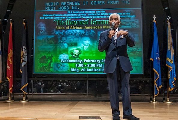Charles Tennant, Sr. addresses the audience gathered in the Building 20 auditorium during the installation's Black History Month observance. Tennant kept the audience riveted will delivering a factual and entertaining history lesson highlighting African American contributions